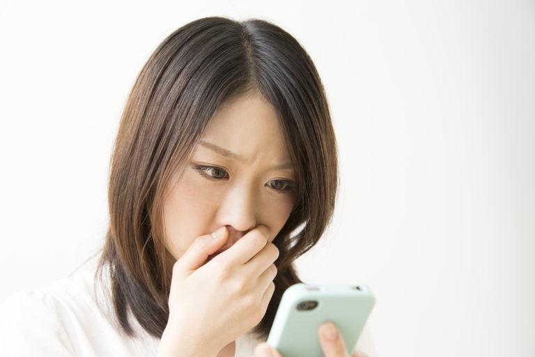 スマートフォンをみて驚く女性