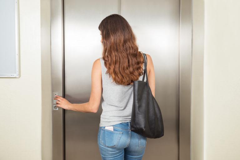 エレベーターを利用するハンドバックの女性