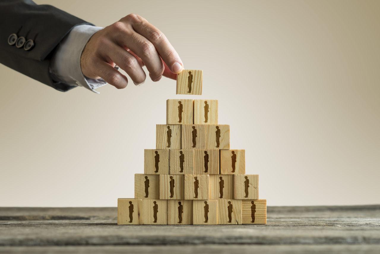 人々のシルエット付きのウッドブロックのピラミッドを構築するビジネスマン