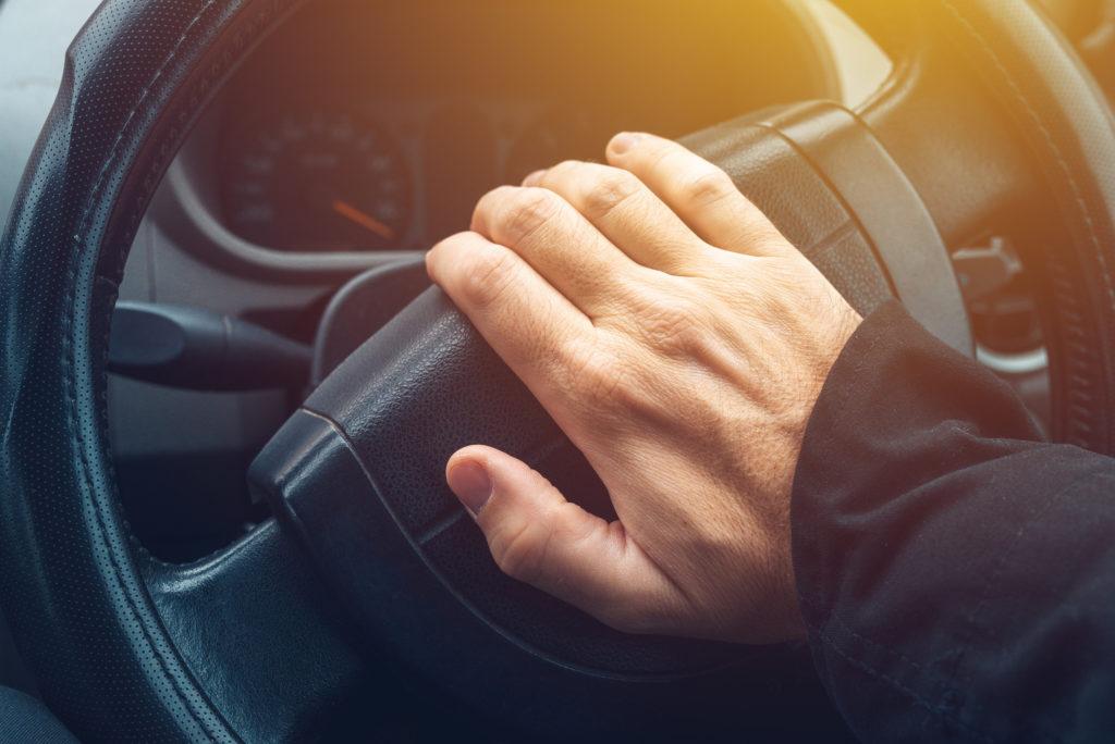 クラクションを鳴らす男性の手