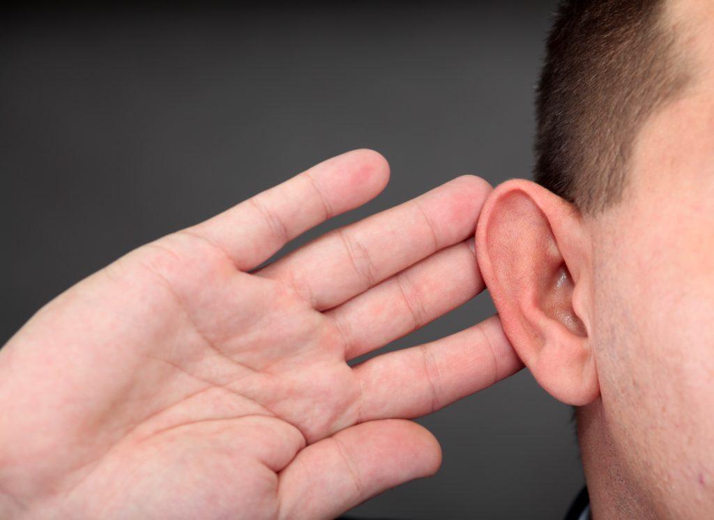 耳に手を当てる男性