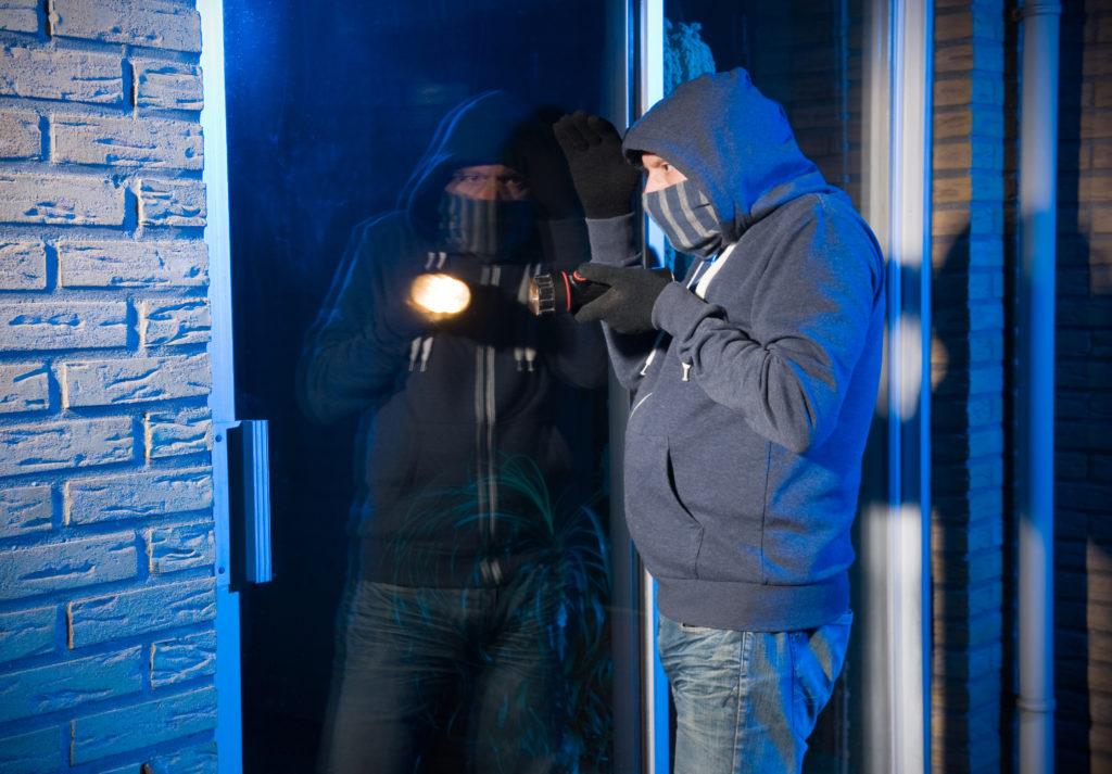 家の窓を覗く泥棒