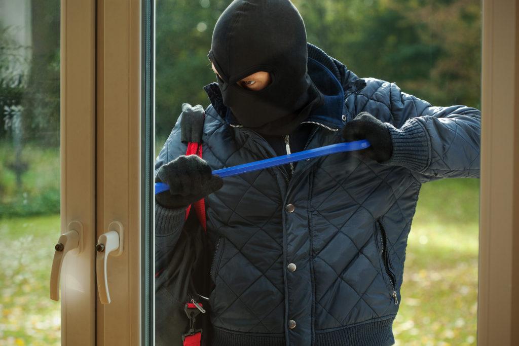 ドアをこじ開けようとする泥棒