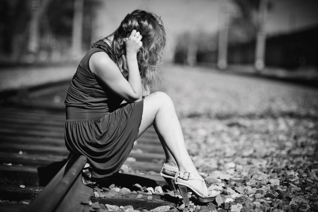 線路に座って悲しむ女性