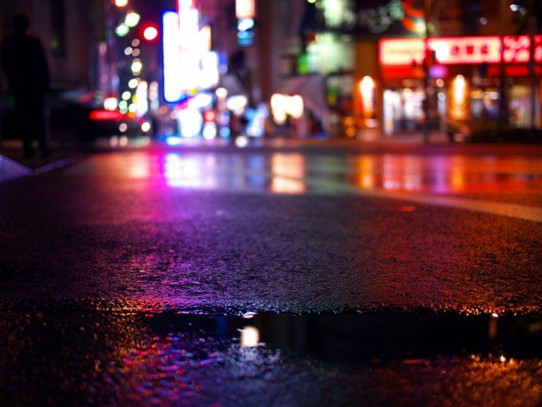都会のネオンが濡れた道路に反射