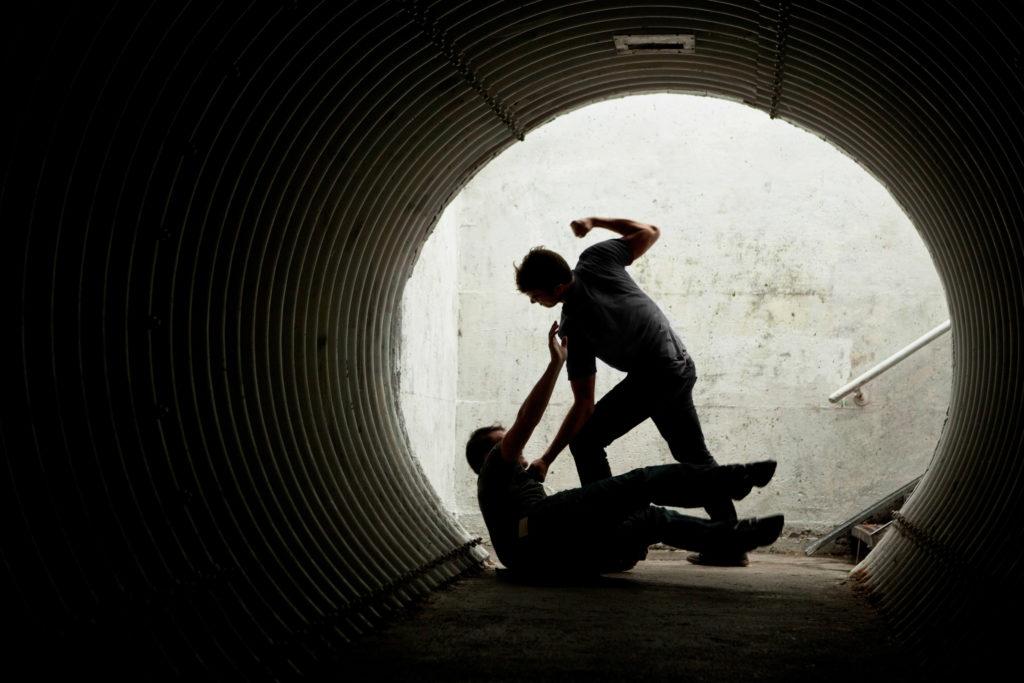 若い男が男性に暴力を振るう