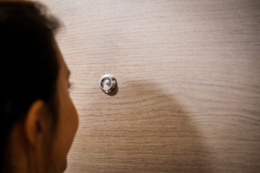 若い女性は彼女の正面玄関ののぞき穴から外を見てします。