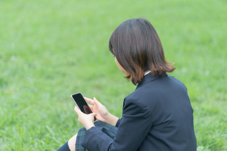 スマートフォンを触る女子高生