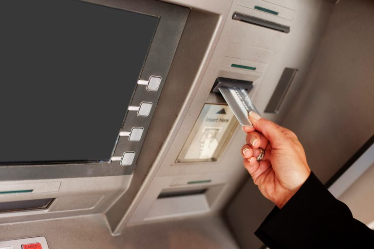 ATM の銀行カードを挿入する女性の手