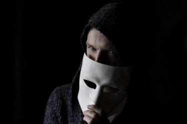 仮面を持った男性