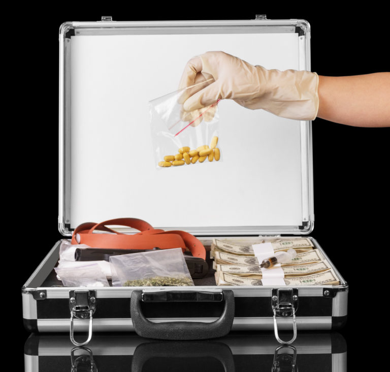 ドル、ピストル、黒い背景に分離された薬剤を持っている手のスーツケース