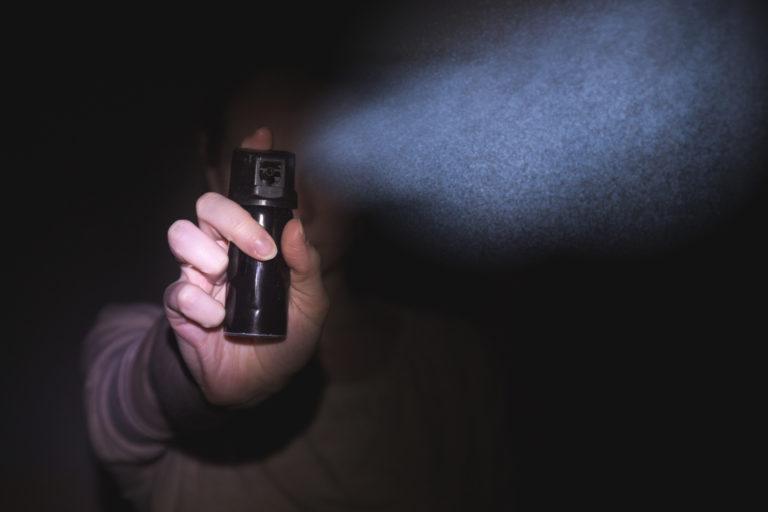 暗闇の中でスプレーを噴射する女性の手